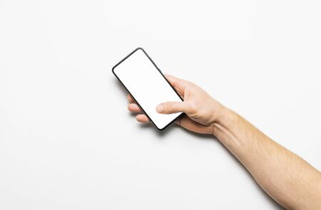 Male hands hold a modern black smartphone with white blank screen on light gray background. Modern technology, phone, gadget in hands, touch screen, template for your design. Mockup. Imagens