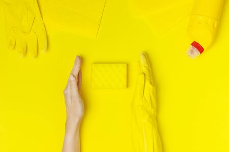 House cleaning concept. Womens hands in yellow rubber gloves, household chemicals, bleach, antibacterial gel, sponge, rags on yellow background. Flat lay top view copy space. Cleaning accessories.