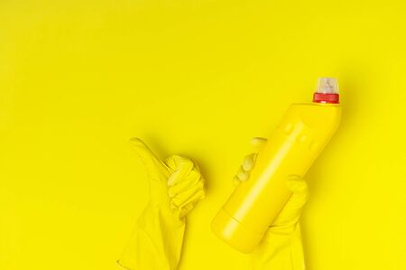 House cleaning concept. Womens hands hold household chemicals disinfectant antibacterial gel yellow rubber gloves sponge rags on yellow background. Flat lay top view copy space. Cleaning accessories.