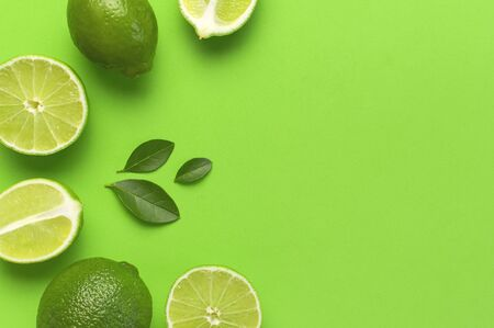 Fresh juicy lime and green leaves on bright green background. Top view flat lay copy space. Creative food background, tropical fruit, vitamin C, citrus. Composition with whole and slices of lime. 写真素材