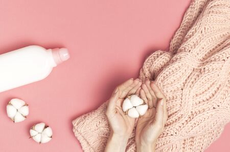 Eco cleaning concept. White plastic packaging of laundry detergent, liquid powder, washing conditioner, knitted wool sweater, cotton flowers on pink background. Flat lay top view. Bio organic product.