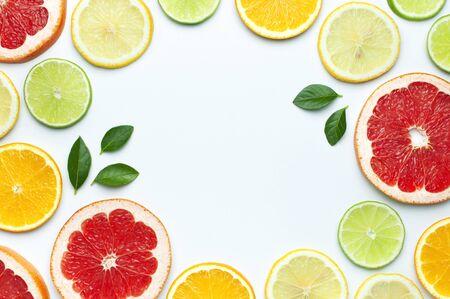 Flache Zusammensetzung mit Scheiben von frischen Zitronen-Orange-Grapefruit-Limonengrünblättern auf weißem Hintergrund Draufsicht Kopienraum. Zitrussaft-Konzept, Vitamin C, Früchte. Kreativer Sommerhintergrund.