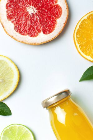 Flat lay composition with glass bottles of juice or fresh, slices of fresh lemon lime orange, green leaves on white background top view copy space. Citrus Juice Concept Vitamin C Fruits. 写真素材