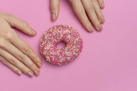 Beautiful female hands with gentle manicure hold sweet donut on pink background top view flat lay copy space. Natural nails, gel polish, self-care, beauty and fashion. Nail care. Donut Background. 写真素材