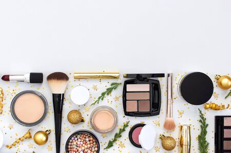 Makeup mascara foundation cream lipstick eyeshadow blush balls and New Year decorations gold Christmas balls confetti stars fir branches on light background Flat lay top view. Cosmetics, holiday Xmas. 写真素材