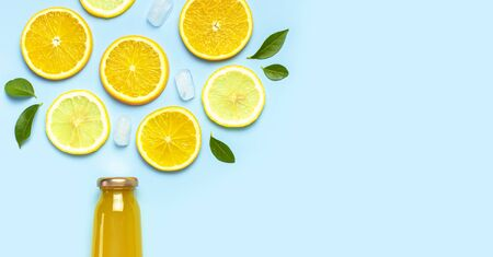 Flat lay composition with glass bottles of juice or fresh, slices of fresh lemon and orange, green leaves, ice cubes on blue background top view copy space. Citrus Juice Concept, Vitamin C, Fruits.
