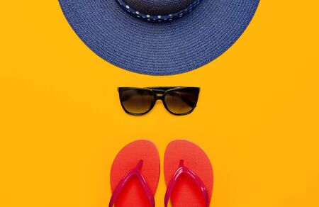 Summer beach sea accessories. Coral flip flops, blue straw hat, sunglasses, shells, starfish on yellow background top view flat lay copy space. Summer background. Holiday vacation travel concept. 写真素材