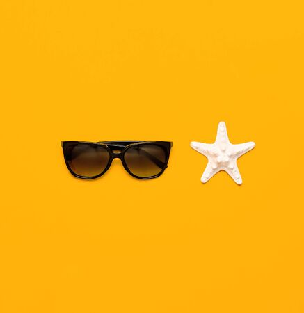 Summer beach sea accessories. Sunglasses, shells, starfish on yellow background top view flat lay copy space. Summer background. Holiday vacation travel concept. 写真素材