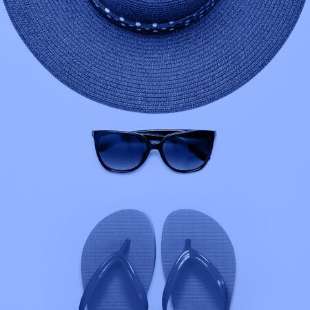 Summer beach sea accessories. Coral flip flops, blue straw hat, sunglasses on blue background top view flat lay copy space. Holiday vacation travel concept. Color of the year 2020 classic blue. 写真素材