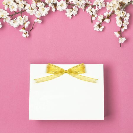 White gift bag with gold ribbon and branch of spring white flowers on bright pink background. Greeting card with delicate flowers Pink floral background. Spring minimal concept. Flat lay top view.