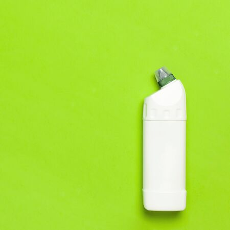 White plastic bottle for liquid detergent, cleaning agent, bleach, antibacterial gel with natural plant extract and green leaves on green background. Eco style cleaning concept. Flat lay top view.