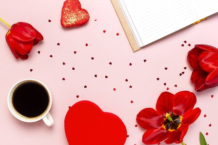 Red tulips, red heart shaped gift box, cup of coffee, blank notebook, macaron cake, confetti on pastel pink background top view Flat lay. Mother's Day Valentines Day birthday holiday background. Foto de archivo - 138472818