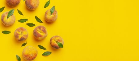 Flat lay composition with peaches. Ripe juicy peaches with green leaves on yellow background. Flat lay, top view, copy space. Fresh organic fruit, vegan food. Juicy Fruit Background.
