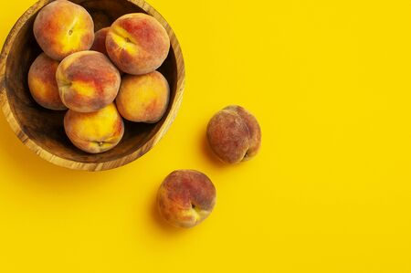 Flat lay composition with peaches. Ripe juicy peaches in wooden bowl on yellow background. Flat lay, top view, copy space. Fresh organic fruit, vegan food. Harvest concept. Fruit Background.