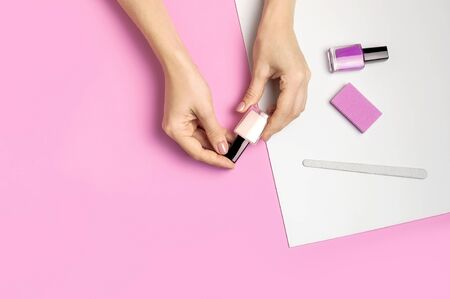 Stylish beautiful gentle manicure. Hands of young woman with nail file, manicure tools on pink background top view flat lay. Natural nails gel polish self-care beauty and fashion. Nail care salon spa. Stock Photo