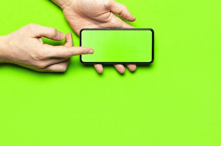 Male hands hold a modern black smartphone with green blank screen on neon green background flat lay top view. Modern technology, phone, gadget in hands, touch screen, template for your design. Mockup.