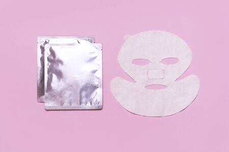 Fabric face mask, clean shiny packaging on pink background. Concept of natural cosmetics, face care, spa, face cream, women's beauty accessories. Flat lay top view copy space. Cosmetics mock-up.