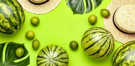 Ripe watermelon berry, summer straw hat, whole limes, tropical leaf monstera on green background top view flat lay. Green Striped Whole Watermelon. Summer bright background. Minimal fruit concept. Imagens