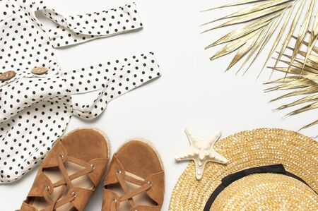 Summer women's white dress in black peas brown sandals straw hat golden palm leaf shells starfish on light background. Flat lay top view copy space. Women's beach fashion travel vacation golden shades.