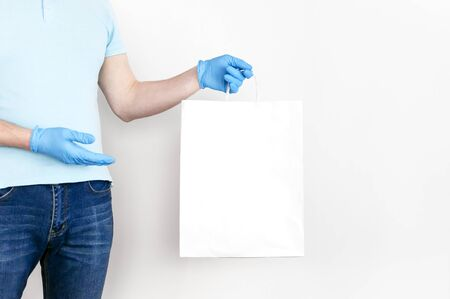 Concept of delivery of goods during quarantine. Young man in blue gloves holds white paper bag in his hands on white background. Delivery against Coronavirus 2019-nCov in pandemic Contactless delivery.