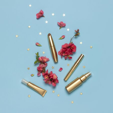 Cosmetics Branding Concept. Cosmetics, spring pink flowers, gold stars confetti on blue background. Cosmetic mock up gold bottles. Flat lay top view copy space. Cosmetic products, beauty background. 免版税图像