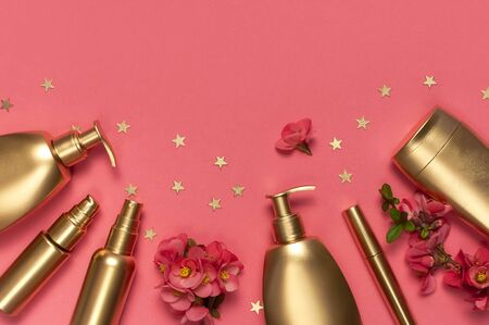 Cosmetics Branding Concept. Cosmetics, spring pink flowers, gold stars confetti on pink background. Cosmetic mock up gold bottles. Flat lay top view copy space. Cosmetic products, beauty background.
