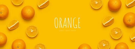 Fresh juicy whole and sliced orange on bright yellow background. Fruit pattern, creative summer concept. Flat lay Top view. Minimalistic background with citrus fruits, vitamin C. Pop art design Banner.