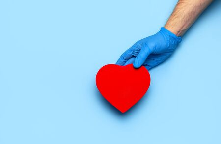 Men's hands in blue medical gloves hold red heart on blue background Flat lay. Concept of saving lives and maintaining health. Doctor's hands with a heart symbol. Medicine, cardiology, love of life. Zdjęcie Seryjne