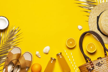 Summer background Beach accessories. Beach wicker straw rattan women's eco bag sandals hat golden tropical leaf coconut orange, juice, straws, shells starfish on yellow background. Flat lay top view.