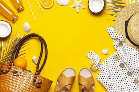 Summer background Beach accessories. Beach wicker straw rattan women's eco bag white dress hat sandals golden tropical leaf coconut orange juice shells starfish on yellow background. Flat lay top view.
