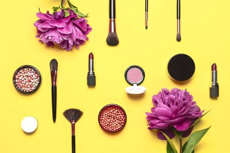 Professional makeup brushes, powder, eyeshadow, blush, lipstick cream on yellow background flat lay top view copy space. Beauty product women's accessory fashion. Different brushes Cosmetic makeup Set.