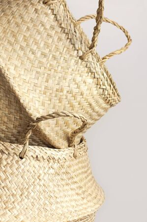 Empty straw wicker basket on a gray background. Fashionable bamboo basket, stylish interior item, eco design, handmade. Natural decor of the interior, home. Natural eco materials, storage basket.