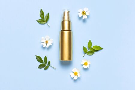 Cosmetic mock up gold bottles. Cosmetics, spring white flowers green leaves on blue background. Cosmetics springtime summer Concept. Flat lay top view copy space. Branding products, beauty background.