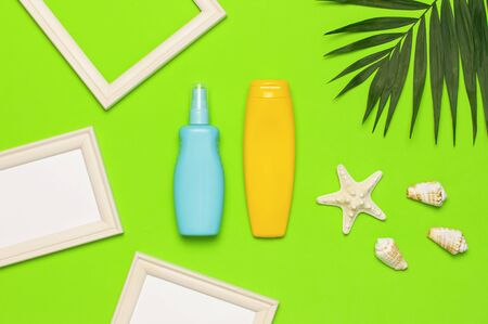 Sun protection Summer background vacation travel concept Yellow blue bottles of sunscreen cream tropical palm leaves shells starfish on green background top view flat lay copy space. Summer cosmetics.