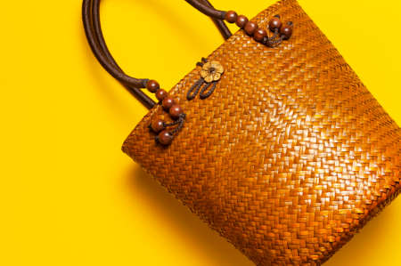 Beach wicker straw or rattan women's eco bag on yellow background. Flat lay top view copy space. Concept of travel. Summer bright background. Beach accessories, women s summer bag, hand bag, fashion. Reklamní fotografie