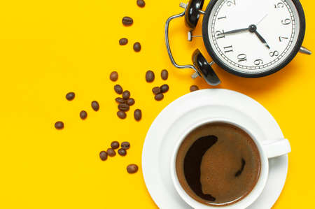 Cup of black coffee, coffee beans, black alarm clock on yellow background Flat lay top view copy space. Minimalistic food concept, morning breakfast, time to work, hot drink, coffee background.