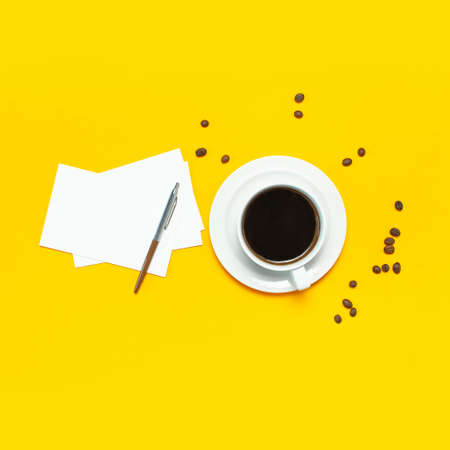 Cup of black coffee, coffee beans, black alarm clock, pens, white paper cards on yellow background Flat lay top view copy space. Creative Concept time to work, female desktop, coffee background. 免版税图像