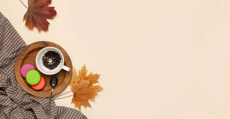 Flat lay autumn composition. White cup with tea leaves, wooden plate, knitted fashion sweater or plaid, pants in a pattern, yellow maple leaves cinnamon orange on beige background top view copy space. 免版税图像