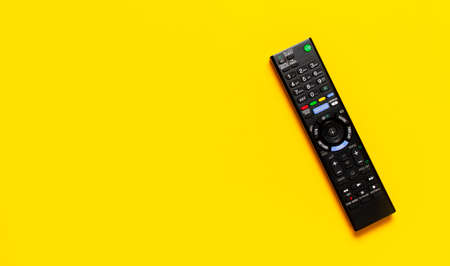 Black TV remote control on bright yellow background flat lay top view copy space. Minimalistic background with a remote control, watching TV, set-top boxes, audio system, soundbar.