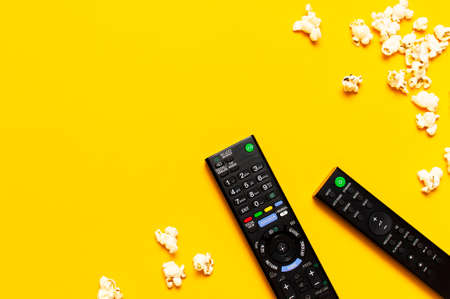 Black TV, audio remote control and popcorn on bright yellow background flat lay top view copy space. Minimalistic background with a remote control, watching a movie, series, set-top boxes, audio system.