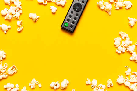 Black TV remote control and popcorn on bright yellow background flat lay top view copy space. Minimalistic background with a remote control, watching a movie, series, set-top boxes, audio system.