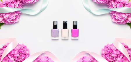 Nail polish, Decorative cosmetics. Set of different varnishes for manicure nails on light background with flowers of pink hydrangea top view Flat lay mock up. Female cosmetics. Beauty blogger concept 免版税图像