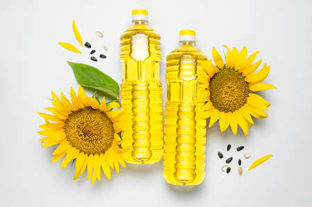 Plastic bottles with sunflower oil, fresh yellow sunflowers, sunflower seeds on gray background. Flat lay top view copy space. Harvest time agriculture farming oil production. Healthy oils, food Imagens