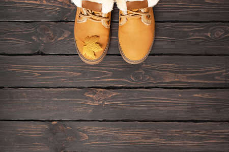 Autumn Fashion Concept. Brown Orange leather women boots with fur, golden autumn leaf on brown wooden background top view copy space. Autumn shoes. Fashionable womens footwear. Cozy fall composition