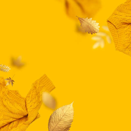 Frame made of orange flying womens knitted sweater and golden autumn leaves on yellow background. Creative clothing concept, trendy fall winter cozy sweater pullover jersey. Female flat lay fashion 免版税图像