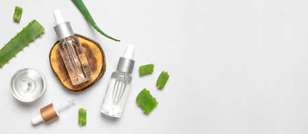 Natural cosmetics concept. Cosmetic oil, serum, gel with aloe vera extract in glass container with pipette on gray background. Organic cosmetics. Top view flat lay. Cosmetics SPA branding mock-up