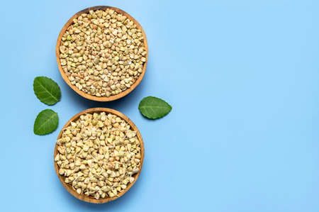Green sprouted buckwheat in wooden bowls with green leaves on blue background. Flat lay top view copy space. Healthy vegan food, eco products, diet, organic. Sprout new life harvest season agriculture