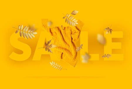 Autumn sale. Fall shopping. Orange flying womens knitted sweater, golden autumn leaves on yellow background. Creative clothing concept trendy fall cozy sweater pullover jersey Female flat lay fashion 免版税图像