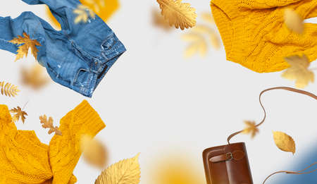 Yellow flying womens knitted sweater blue jeans brown leather bag golden autumn leaves on gray background. Creative clothing concept, trendy fall cozy sweater pullover jersey. Female flat lay fashion