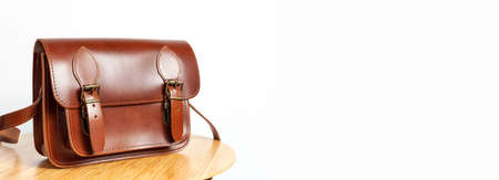 Fashionable brown womens bag made of genuine leather on wooden table against white wall with place for text. Fashion concept. Details of leather bag belt metal buckle clasp. Stylish female accessory 免版税图像